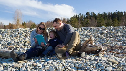 Family of three sitting on the stony shore and watching
