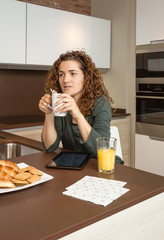 Tired young girl with cup of coffee in a breakfast