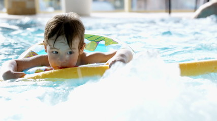 Little boy swimming in the pool with rubber ring