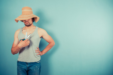 Man wearing beach hat is holding scissors