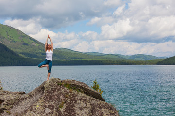 Young woman is practicing yoga in high mountains