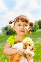 Looking small girl hugging rabbit in green field
