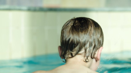 Back view of a kid swimming in rubber ring in the pool