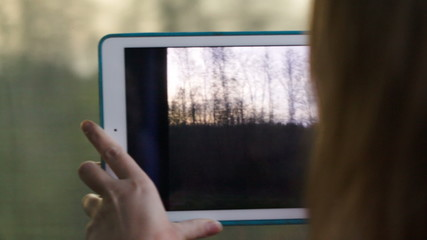 Woman with pad in the train making a video of passing landscape