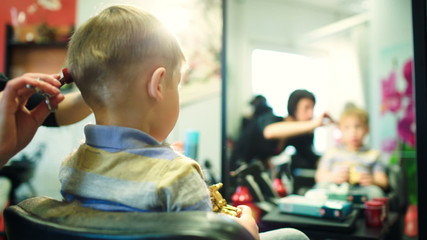 Hairdresser cutting childs hair while he playing with a toy