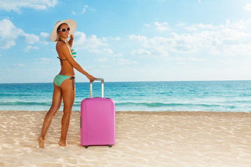 Beach girl with pink luggage near the sea
