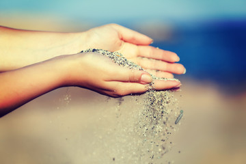 A woman with sand falling through her hands
