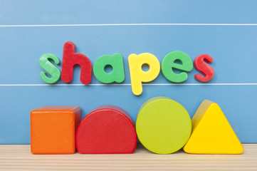 Colorful magnetic letter spelling the wordshapes on blue board