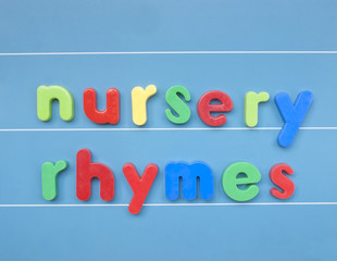 Colorful magnetic letters spelling nursery rhymes on blue board