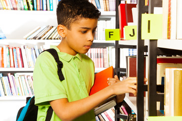 Boy searches books on library bookshelf