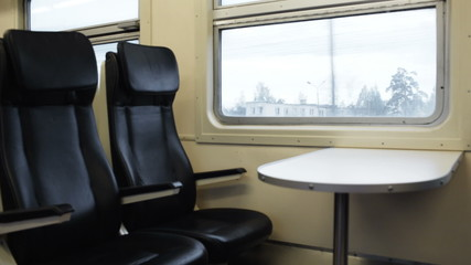 Two empty seats with table in the moving train