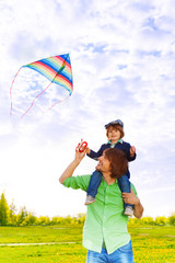 Father holds kid on shoulders with flying kite