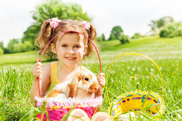 Smiling girl with cute rabbit and baskets in park