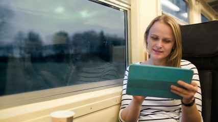 Woman with touchpad and tea in the train in the evening