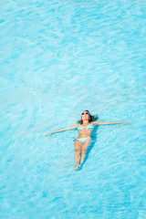 Woman with sunglasses swimming in the pool