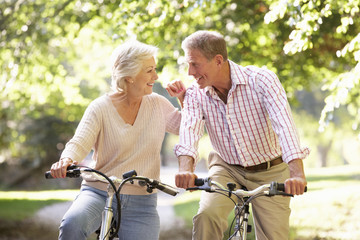 Senior couple cycling in park
