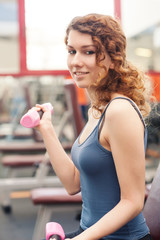 Young woman exercising with dumbbells in the gym.