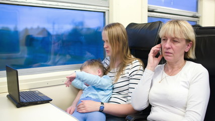 Passengers in the train watching video on laptop and talking on