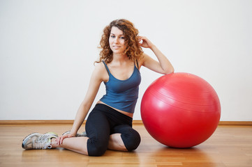 Young woman portrait with ball in the gym.