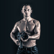 Confident young man shirtless portrait with machine gun against