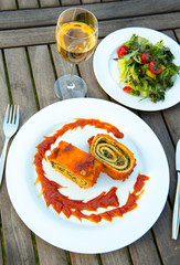 filled pasta with salad and wine