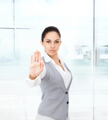 Serious business woman making stop hand sign