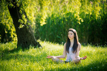 Beautiful young woman doing yoga, sitting in lotus position on g