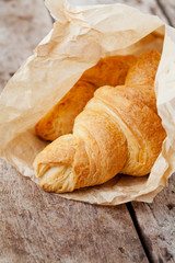Fresh croissants in paper bag on wooden background
