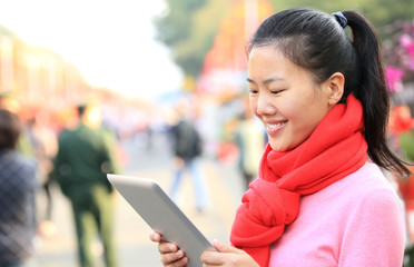 young asian woman use digital tablet on streeet