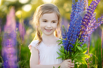 Cute girl in blooming lupine field