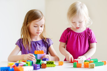 Two little sisters plaing with colorful blocks