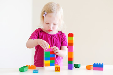 Cute toddler girl plaing with colorful blocks