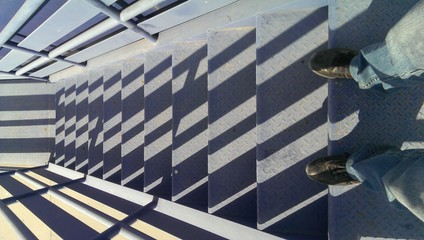 Looking down on blue stairs with shadows