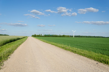 Rural gravel road near fields and windmill