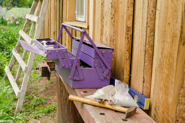 purple toolbox hammer nail on wooden table outdoor