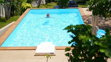 Woman Swimming in the Resort Outdoor Pool. Sunny Summer