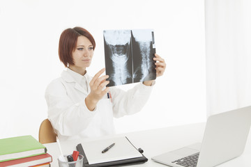 Medical expert looking at x-ray scan while sitting at desk