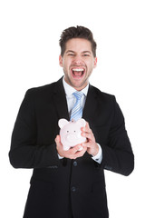 Cheerful Young Businessman Holding Piggybank