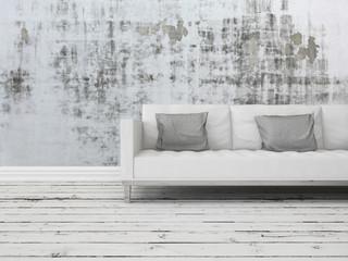 Weiße Couch steht vor heruntergekommener Betonwand