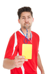 Referee Blowing Whistle While Showing Yellow Card