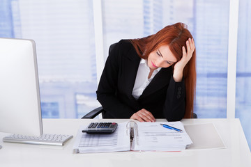 Tensed Businesswoman At Office Desk