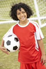 Portrait boy in football kit with ball