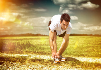 Athlete pausing to tie his laces on a morning run