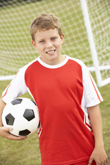 Portrait boy in soccer kit with ball