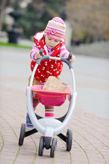 baby girl with toy stroller
