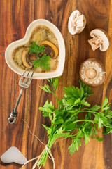 Mushroom casserole  with fresh parsley on brown wooden board
