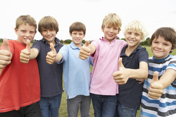Portrait group of boys doing thumbs up in park