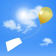 Gelber Luftballon vor blauem Himmel