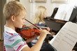 Boy and girl playing violin and piano at home