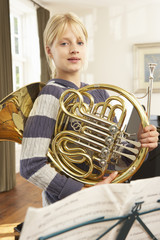 Girl holding French horn at home